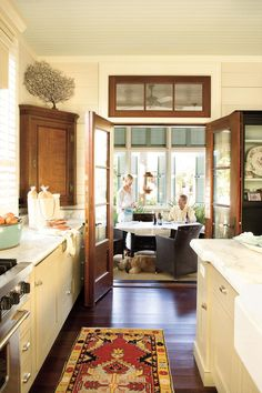French doors open directly from the kitchen to a front porch dining area that acts as an extension of this home's interior. It's an inviting place for a morning paper and evening entertaining alike.    Tour this Coastal-Style Home