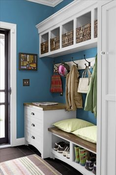 White and blue mud room.  This little mudroom is beutifully made with white and blue color palette, basket storage, big hooks to hang up coats, easy to clean black flooring, bench. A cozy bench allows you to perch while you pull your boots on. Looks so welcoming.