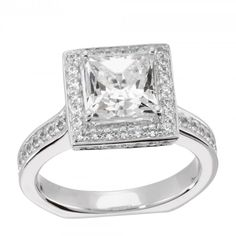 A modern take on the halo, this ring features a Princess cut Contemporary Nexus Diamond™ in a squared halo. The shoulders of the shank lift the halo high into to the light, creating an open profile with a surprise bezel set accent stone. The band features a Euro style design, with a flat bottom that makes it comfortable to wear.  Center stone is available in a variety of carat weights; choose yours from the menu above. Complete the look with the matching Black Magic band. Order additional…