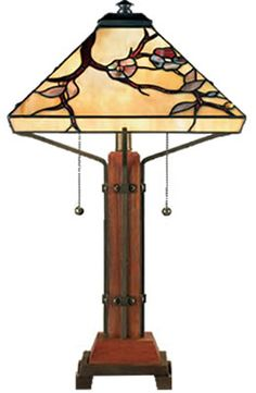 "Quoizel Arts & Crafts Style Table Lamp $530. This Arts & Crafts piece features a shade with flowering tree pattern, handcrafted from genuine art glass in hues of amber, wine, steel blue and hunter green. The wood base has geometric iron accents, adding to its natural, earthy, organic style. Shade is genuine art glass in hues of amber, wine, steel blue and hunter green. 23.5""x14""."
