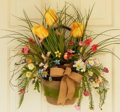 CLICK HERE https://www.etsy.com/shop/PataylaFloralDesigns?ref=si_shop for more floral designs Wreath Twig Basket Door Decor Wall Hanging This floral design can be a floral arrangement for a side table, an outside door wreath, or inside wall decor.  Made in a twig moss basket, embellished with a large band of burlap with a green ribbon. If used as a wall hanging or outdoor door decor it can easily be hung by the basket handle.  Tulips, cosmos, cherry blossoms, ferns, field flowers, bird nest.