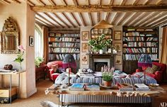 The living room's reclaimed-wood sofa table and shelving echo the timeworn ceiling beams. Cheerful red armchairs and antique herbarium specimens flank the fireplace. A glamorous Louis XV gilt-wood mirror (at left) gleams against walls of unpainted plaster.