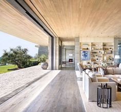 concrete floors glass walls and textured timber ceilings creating expansive open plan interiors