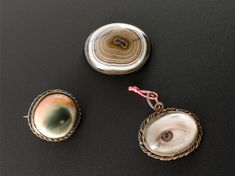 Shell pendant (right) painted with an eye, Paris, France, 1850-1920; this, and the two other amulets were worn to ward off the evil eye and eye infections. (Science Museum, London, via the Wellcome Collection)