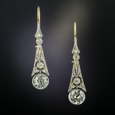 In these exquisite drop earrings, weve joined a nearly perfectly matched pair of beaming bright white and sparkling old European-cut diamonds--one weighing 1.00 carat, the other 1.01 carat--to sleekly styled, late-Edwardian/early-Art Deco diamond-set tops (hand fabricated in platinum over 18K gold). Long and lovely, they measure 1 1/4 inches long, dropping down a bit further from the newer and beautifully crafted14K gold ear wires. Total diamond weight, 2.47 carats.
