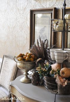 pheasant and turkey feathers among tarnished silver, acorns, fruit, berries, and other seasonal elements for a fall mantle display