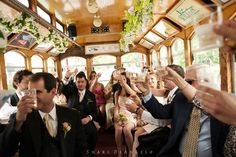 Traveling inside a trolley en route to a Nassau Inn wedding in Princeton, NJ, the bridal party and family raise their glasses in toast to the new couple. The trolley has been decorated in the wedding colors of ivory and pale pink, with a garland of white anemones draped overhead, contrasting with the oak wood paneling. Upon arriving at the reception, the guests danced all night long to the sounds of the John Parker Band. http://www.jpband.com/weddings.html