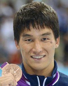 男子200メートルバタフライで獲得した銅メダルを手に笑顔の松田丈志=水泳センター(共同)