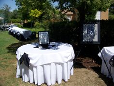 Memory Table with Buffet in Background.  Buffet Table draped in the reverse - Black Linens w/ White Toppers