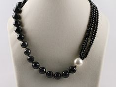 black beads necklace, one white pearl