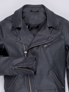 A biker jacket made with black, coated denim. It features all the classic hallmarks of the classics, from the offcentre zip fastening to the wide notch lapels and the three zip front-pockets and a fl