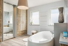 Primary bathroom with a large modern freestanding tub and a walk-in shower room, along with a rustic reach-in closet. Soaker Tub Free Standing, Bathroom Shop, Bathrooms, Bathroom Closet, White Master Bathroom, Bathroom Showrooms, Faux Wood Blinds, Shower Cubicles, Modern Bathroom Design