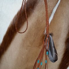 The Prairie Necklace  Beauty in simplicity…  Beauty in nature… The Prairie Necklace by Double R.  A long, braided neckpiece in tan deerskin leather, wrapped together with more leather, with long tassel ends and turquoise-colored howlite beads.  Lastly, accented with a genuinely beautiful, natural feather.  Versatile… natural… ageless…