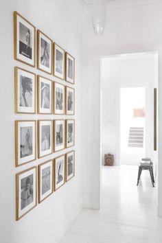 galeria czarno-białej fotografi w drewnianych ramkach na białej ścianie w przedpokoju