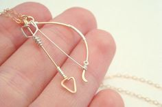 Archery bow and arrow necklace - Elven fantasy hunting weapon in 14k gold filled wire and sterling silver. $40.00, via Etsy.