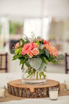 (Foto 1 de 10) Centro de mesa con rosas y hojas verdes. Peana de madera en forma redonda, Galeria de fotos de Centros de mesa de estilo rústico para tu banquete de boda