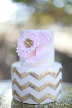 Pink, gold, and white chevron cake complete with a flower for an engagement session.