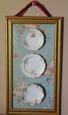 Shabby chic display of vintage-look plates & wallpaper in a gold frame