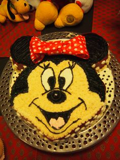 """Minnie Mouse cake using a simple 12"""" round pan and 4"""" round pans.Carved the shape after freezing the cake and decirated with Homemade buttercream icing."""