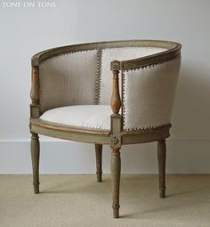 A charming French early painted tub chair reupholstered in vintage linen and finished with tacks. via Tone on Tone