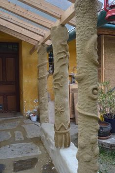 Columns made of cob (around wooden posts and reed-stucco) on earthbag-foundation-wall | Säulen aus Strohlehm (Cob) um Holzständer und Schilfstukkatur auf earthbag-Mauer/Fundament