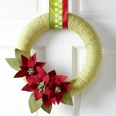DIY Festive Yarn Wreath --  Greet rosy-cheeked guests with a warm, flowery wreath. First, wrap green yarn around a wreath form (available at your local crafts store). Then, create the pretty poinsettia blooms by cutting out felt flower shapes and hot-glueing silver bells to the centers. Hang from your door with a festive red-and-green ribbon.