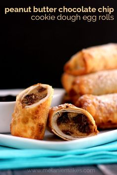 Rich and melty peanut butter chocolate chip cookie dough is wrapped in a crisp egg roll wrapper and sprinkled with powdered sugar.  Dipped in chocolate ganache, these Peanut Butter Chocolate Chip Cookie Dough Egg Rolls are the excuse you've been waiting for to enjoy cookie dough, bite after decadent bite.