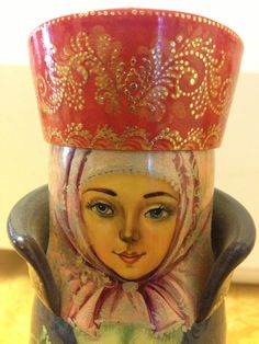 This is a beautiful one-of-a-kind Russian Lacquer hand painted decorative bottle holder. Marina is the most famous Russian artist that paints wooden santas. She has some Russian Stacking Dolls and lacquered boxes as well. This was unusual for her to paint this piece. Kind of like when the artistic spirit strikes you. Her pieces are seen in fine art galleries, book as well as museums and can go for tens for thousands of dollars. She is very well known in Russian and all over the world.