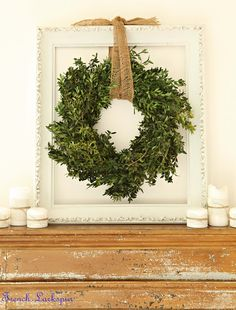 Boxwood wreath suspended in empty white frame with pretty gold ribbon...