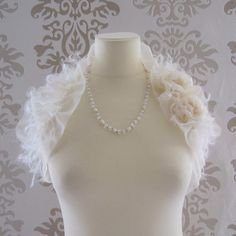 A chic shawl/wrap in light cream chiffon with ruffle and mohair for a dreamy look. Adorned with 2 handmade pearled rosette. This piece simply wraps ar