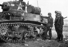 German soldiers inspect a knocked-out stuart tank
