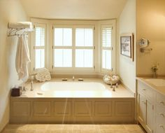 "Crown Point; ""A bathroom solution to ""how do we access the plumbing under the built-in tub?"" Appearing similar to wainscoting, the arrangement of multiple working doors allows an easy way in. Touch latches on the bath cabinets eliminate the need for protruding knobs or pulls."""
