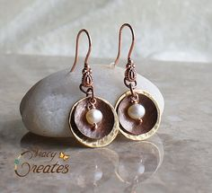 These beautiful brass and copper hammered discs encompass a cultured white freshwater pearl. They dangle from a fancy copper earwire. The