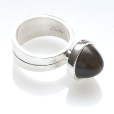 Sterling sliver ring with cabochon Tiger Eye. In the late 1960's Jens greatly enjoyed working with cabochon stone settings, due to their non-conforming contemporary style and their availability. The silver cup is bevelled to hold the cabochon stone firmly, a technique Jens was particularly talented at.   Approx price $899