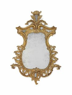 A GEORGE II GILTWOOD MIRROR MID-18TH CENTURY - The waisted central later plate within a C-scroll and rockwork-carved frame enclosing border plates, with acanthus spray cresting, inscribed to the reverse '*gham 67', re-gilt - Dim: 46 x 32 in. (117 x 81 cm.)
