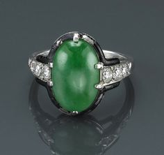 An art deco jadeite jade, diamond and enamel ring, Cartier, circa 1925  centering an oval-shaped jadeite jade; signed Cartier, no. 4953; mounted in platinum; size: 6 (heavy loss to enamel. http://www.bonhams.com/auctions/18681/lot/502/?page_anchor=MR1_page_lots%3D7%26MR1_results_per_page%3D50%26MR1_module_instance_reference%3D1