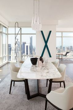 With gorgeous city views through the panoramic floor-to-ceiling windows of this apartment designed by Tara Benet, not much adornment is needed. The graphic X and more delicate but just as large wire piece by Valentin Carron make strong graphic statements that complement rather than detract in this dining room.