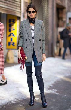 Street style look de Leandra Medine usando blazer alfaiataria xadrez, calça jeans, bota over the knee preta, lenço no pescoço e maxi clutch com franjas.