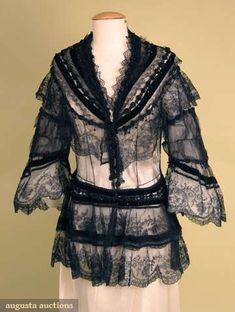 Black Lace Evening Jacket, 1860's:  Black cotton net, Chantilly lace flounces, narrow black bobbin lace, black velvet bands below silk trim w/ jet beads, fitted back w/ long peplum, 3/4 bell sleeve.