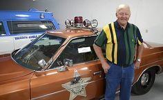 """ADVANCE FOR MONDAY JULY29 - Former Warren, Minn. Sheriff Dennis Brekke stands on July 25, 2013, in Warren, Minn.with the famous """"UFO Car"""" a Sheriff's vehicle driven by deputy Val Johnson that was supposedly struck by a UFO in 1974. Brekke was present after the encounter that evening and said Johnson's incident began with a bright light Johnson decided to scope out, which led to the foreign object's collision with the car, leaving a shattered headlight, dented hood, cracked windshild and two…"""