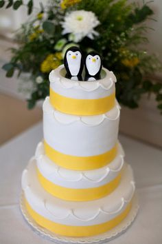 a yellow wedding cake with the wedding topper a pair of penguins-now that's adorable.