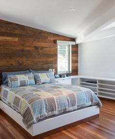 In this contemporary master bedroom, a wood accent wall and wood flooring add a natural touch to the all wall white room. #MasterBedroom #WoodAccentWall