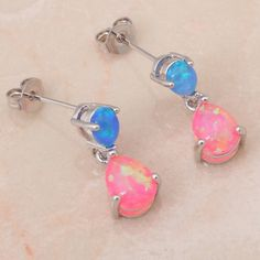 Adorned with brilliant blue and pink opals, these drop earrings illuminate from every angle and will add flirty appeal to your ensemble. EARRING DETAILS - Size: 18 mm x 6 mm - Backings: post - Metal: