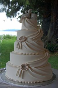A glam Wedding cake- add broches at the corners of the drapes and flowers at the top