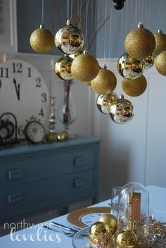 hang gold & silver ornaments with a little bling beads on a large painted tree branch in corner of room