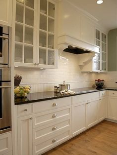 sage green walls paint color white glassfront kitchen cabinets polished black granite countertops subway tiles backsplash and oak hardwood floors