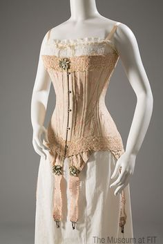 "Corset and chemise, circa 1905. #lingeriehistory From the Collection of The Museum at FIT / Early twentieth-century corsets rested low on the bosom, and extended over the hips. When laced, the so-called ""straight-front"" corset provided an ""S curve"" that pushed the breasts forward, pressed in the stomach, and arched the back."