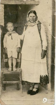 A B/W photo of a woman in Attica costume and a little boy.