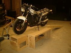 Collapsible Motorcycle Workstand: The workstand is constructed from two full sheets of plywood. To build the workstand you will need: Two sheets of inch plywood. One lb box of 1 inch drywall screws per bench being built One small bottle of woodglue. Motorcycle Ramp, Motorcycle Lift Table, Bike Lift, Motorcycle Workshop, Womens Motorcycle Helmets, Cruiser Motorcycle, Motorcycle Girls, Motorcycle Wiring, Motorcycle Trailer