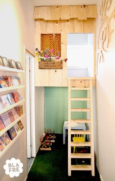 Lofted hideaway with play space underneath. Love the book storage along the wall, too.